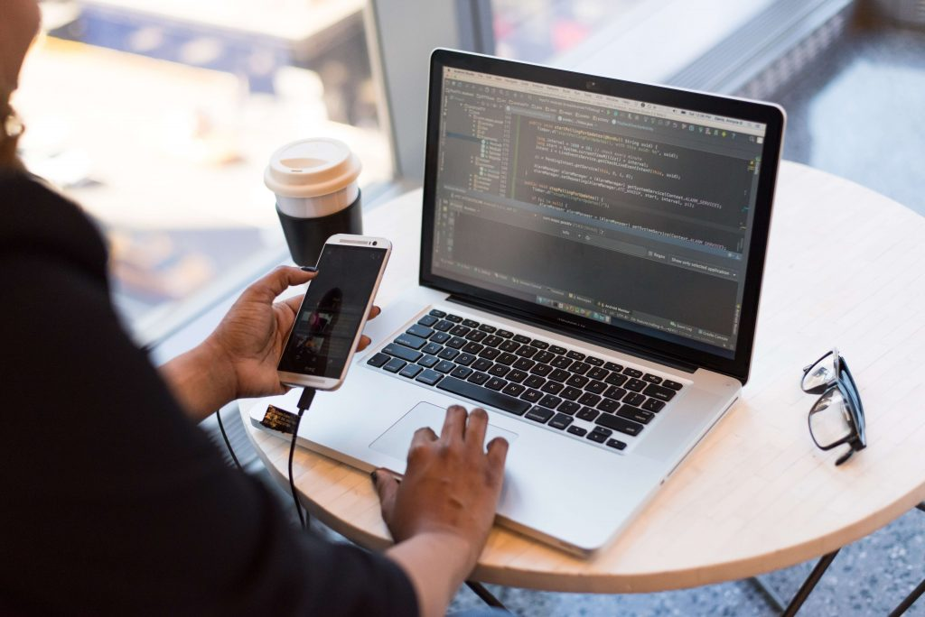 Image of a woman on her iPhone and MacBook.